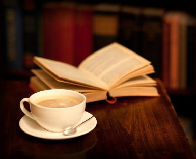 na stole leży otwarta książka, przed nią filiżanka z kawą