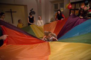 opis zdjęcia: kolorowa chusta animacyjna kalanza naciągnięta przez wolontariuszy w różnych strojach karnawałowych pośrodku uniesiony na chuście chłopczyk przebrany za amorka.