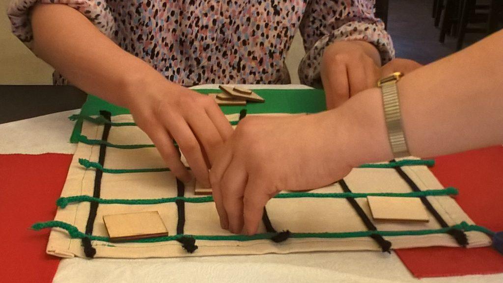 opis zdjęcia:  plansz do gry memory, rozłożone elementy gry i dłonie graczy sprawdzające ruch gry.