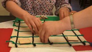 Opis zdjęcia: plansza do gry Memory, dwie dłonie różnych osób oglądają pola z elementami gry.