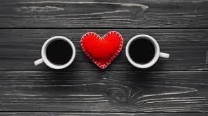 Opis zdjęcia: na ciemnych deskach, patrząc z góry dwie białe filiżanki z kawą, pomiędzy nimi czerwone uszyte ręcznie serce.