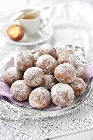 Opis zdjęcia: na talerzu małe pączki posypane cukrem pudrem