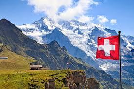 opis zdjęcia : malowniczy krajobraz  szczytów alpejskich, na pierwszym planie powiewa flaga Szwajcarii: na planie kwadratu w kolorze czerwonym, wpisany biały krzyż grecki.