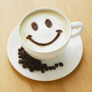 Opis zdjęcia: na stole biała filiżanka z kawą ze spienionym mlekiem, na którym narysowany są oczy i uśmiech, na spodeczku rozsypane ziarenka kawy.