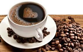 Opis zdjęcia: na stole rozsypane ziarenka kawy pośród nich filiżanka z kawą, na jej powierzchni z pianki utworzone serduszko.