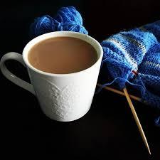 Na ciemnym stole filiżanka kawy, tuż przy niej rozpoczęta robótka ręczna z włóczki o niebieskich odcieniach