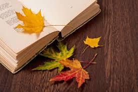 Na stole rozłożona książka, na niej i wokół niej rozrzucone jesienne liście.
