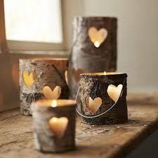 cztery różnej wysokości lampiony z drewna, z wyciętymi otworami w kształcie serca, przez które widać płonień świecy.