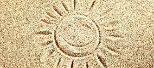 na piasku narysowane uśmiechnięte słońce.