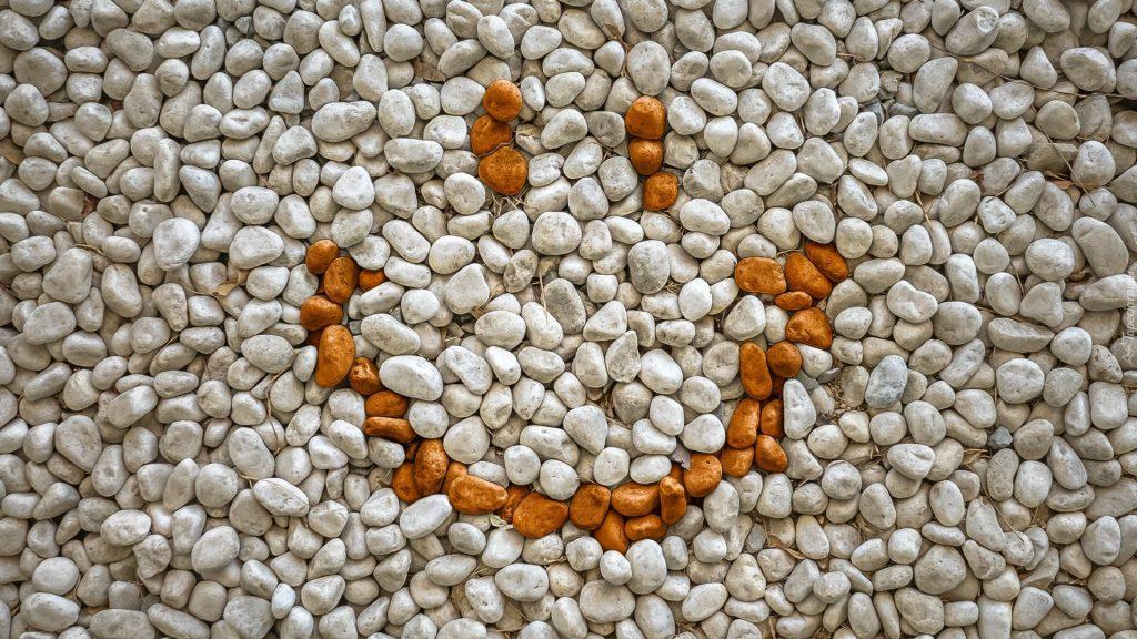 drobne kamyczki beżowego koloru wypełniające tło, z  miodowych kamyczków ułożony uśmiech