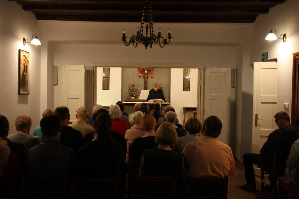 Kaplica w domu rekolekcyjnym w Laskach, od tyłu sylwetki siedzących ludzi przodem do słuchaczy przy ołtarzu  ksiądz.