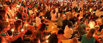 Młodzież w półmroku siedzi po turecku z płonącymi świeczkami na spotkaniu modlitewnym w ducchu Taizé.