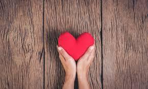 Opis zdjęcia: na tle desek wyciągnięte dłonie, trzymające serce.