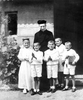 Ks. Stefan Wyszyński, na tle kaplicy w Laskach z dziećmi pierwszokomunijnymi