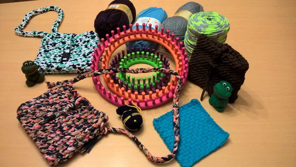 rozłożone na stole: obręcze dziewiarskie, różnokolorowe motki włóczki oraz wyroby dziewiarskie: torebki, miękkie zabawki i serwetki