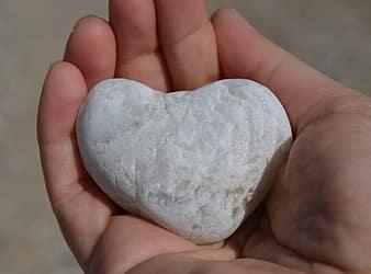 Na wyciągniętej dłoni biały kamień w kształcie serca
