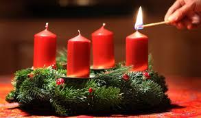 Wieniec adwentowy z czterema czerwonymi świecami, jedna z nich zapalana jest zapałką