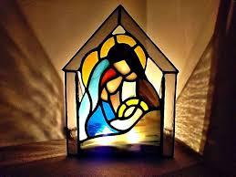 Witraż - szopka, kolorowe szkiełka z konturem Świętej Rodziny, rozświetlone światłem.