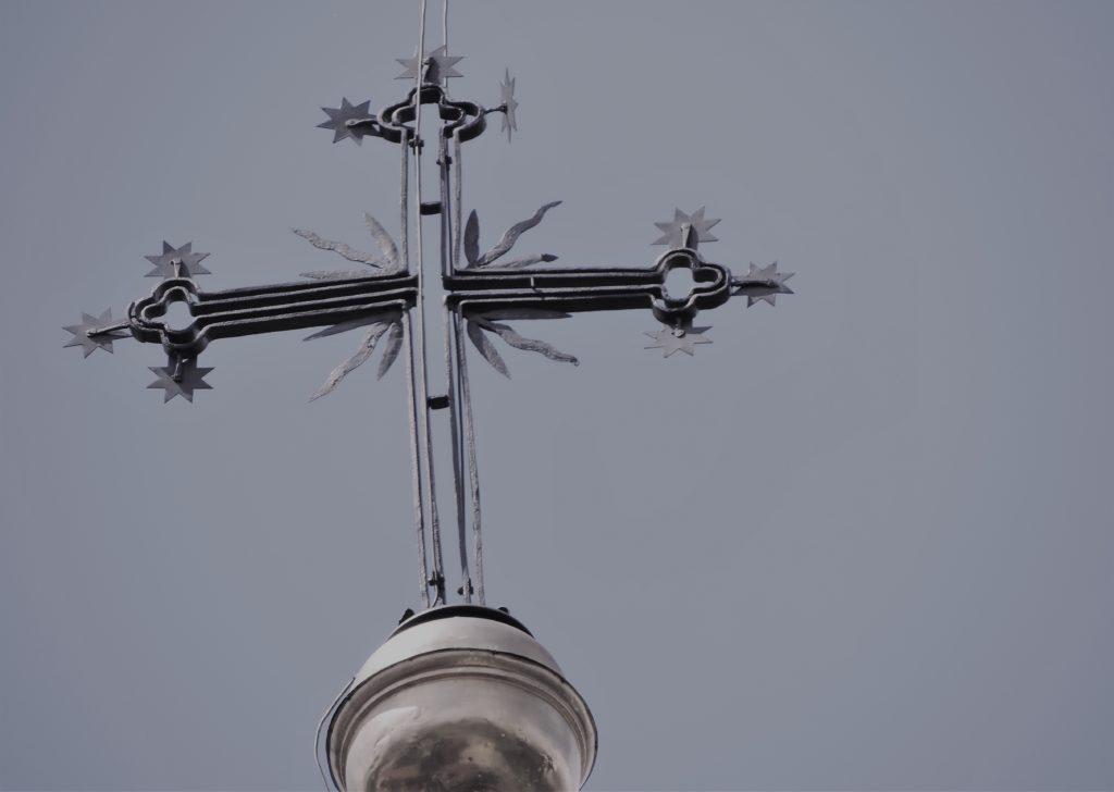 Na szarym niebie, metalowy krzyż