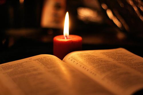 Otarta księga Pisma Świętego, za nią płonąca świeca.