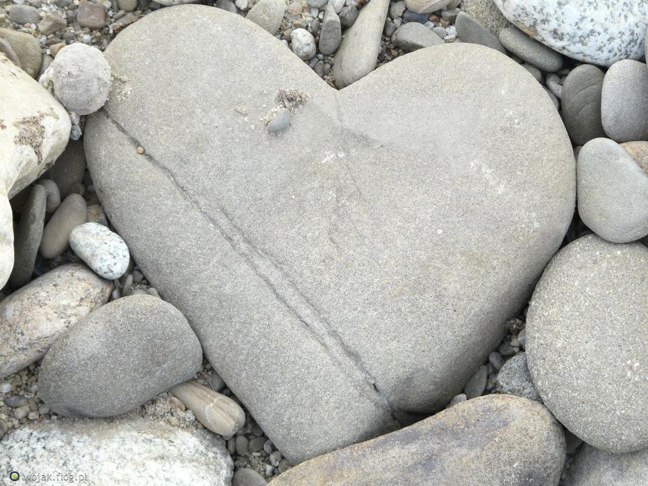 wśród szarych drobnych kamieni, większy kamień w kształcie serca