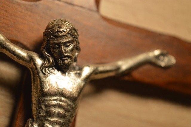 W przybliżeniu fragment drewnianego brązowego krzyża, na nim postać Chrystusa ukrzyżowanego.