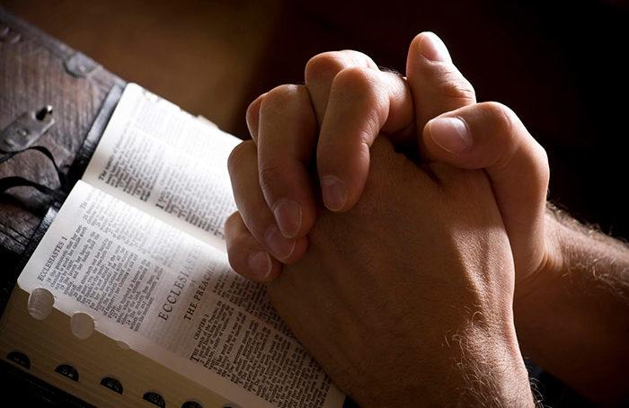 Na otwartej księdze Pisma Świętego, złożone dłonie w geście modlitwy.