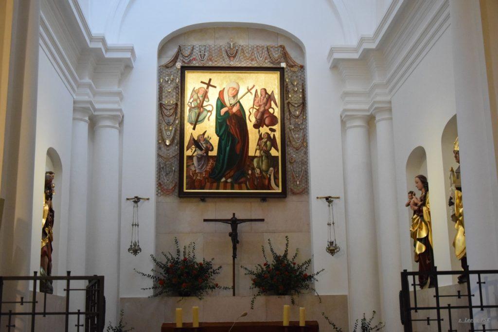 Obraz Matki Bożej Pocieszenia w nawie bocznej w kościele św. Marcina, przyozdobiony bukietami z czerwonych róż.