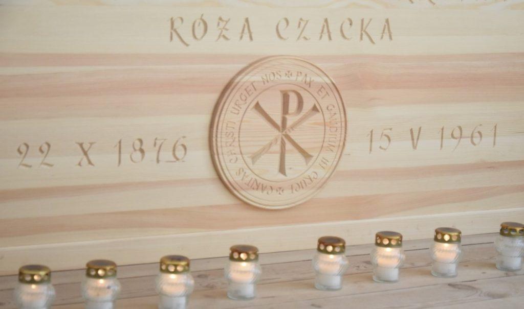Fragment sarkofagu Sługi Bożej Matki Elżbiety Czackiej wykonany z jasnego drewna, widoczny napis Róża Czacka data urodzin i śmierci, rozdzielona godłem Zgromadzenia.