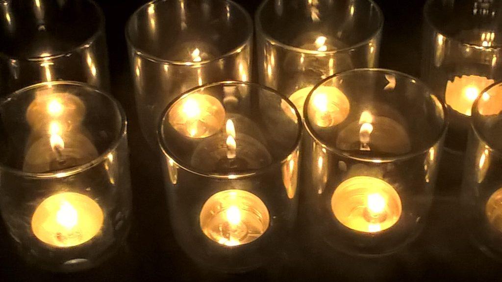 palące się świece w szkle, ustawione w kilku rzędach