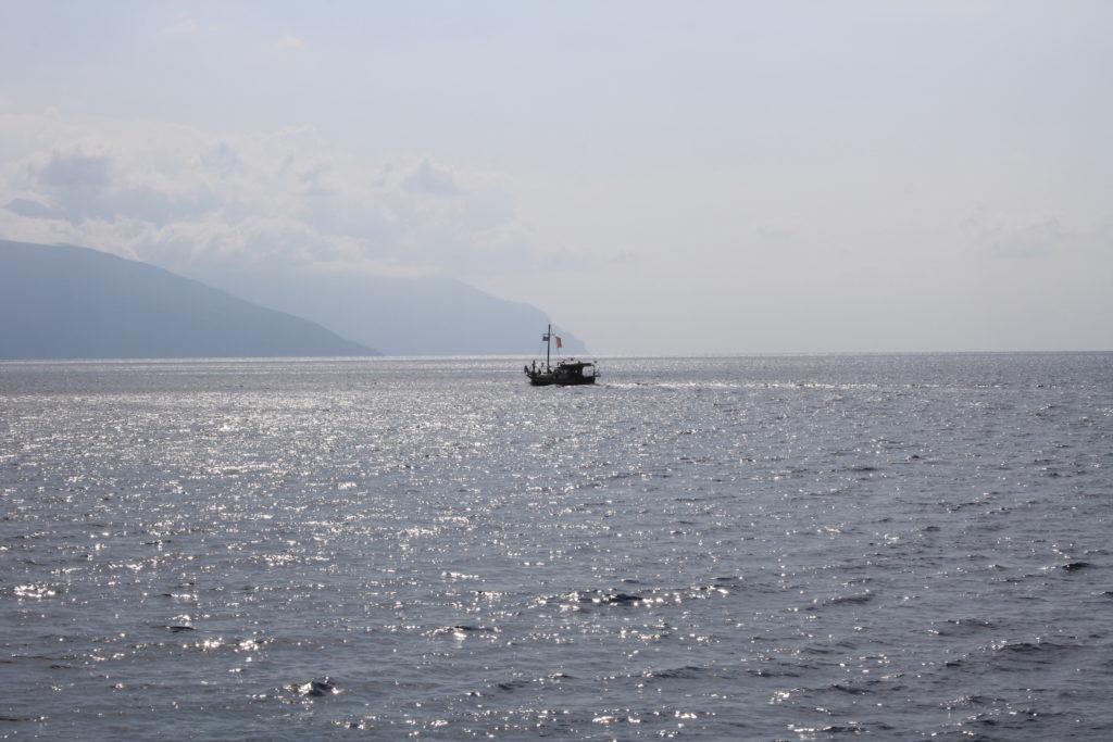 Na spokojnym morzu, na którym odbijają się promienie słońca, w oddali płynący kuter rybacki.