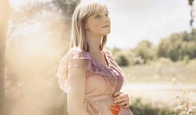 młoda kobieta oczekująca dziecka, z dłońmi na ciążowym brzuchu, na sukience przyklejone ma czerwone serduszko z imieniem Franek