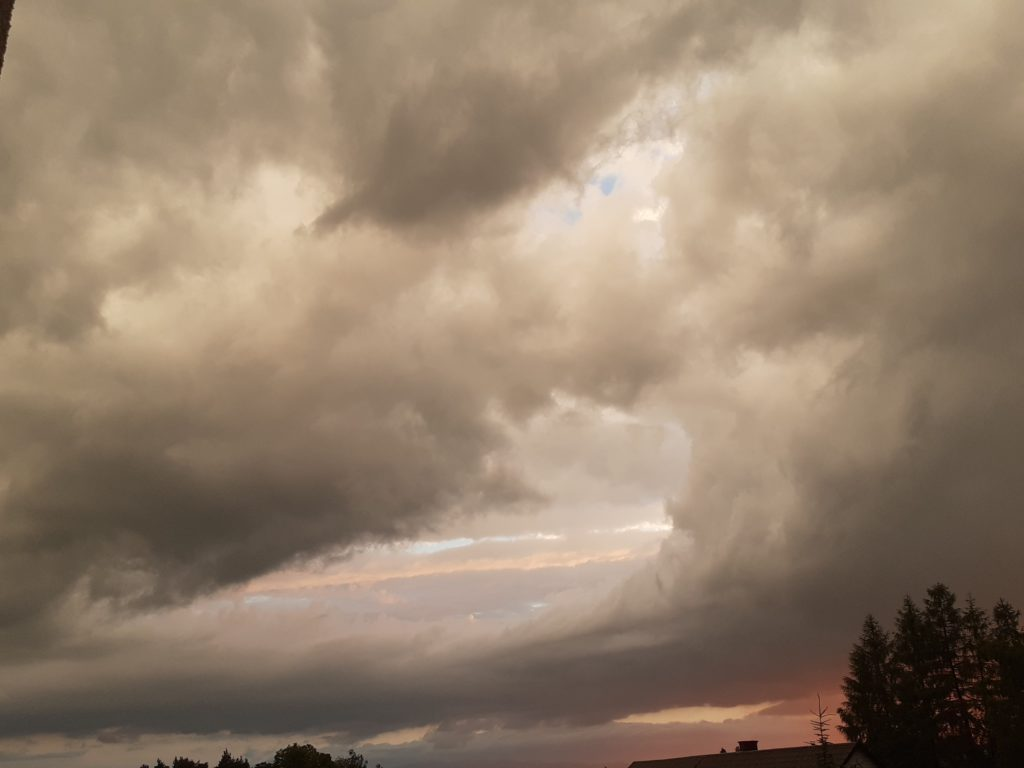 wieczorne niebo z kłębiącymi się chmurami po burzy, w odcieniach szarości i pomarańczowego koloru