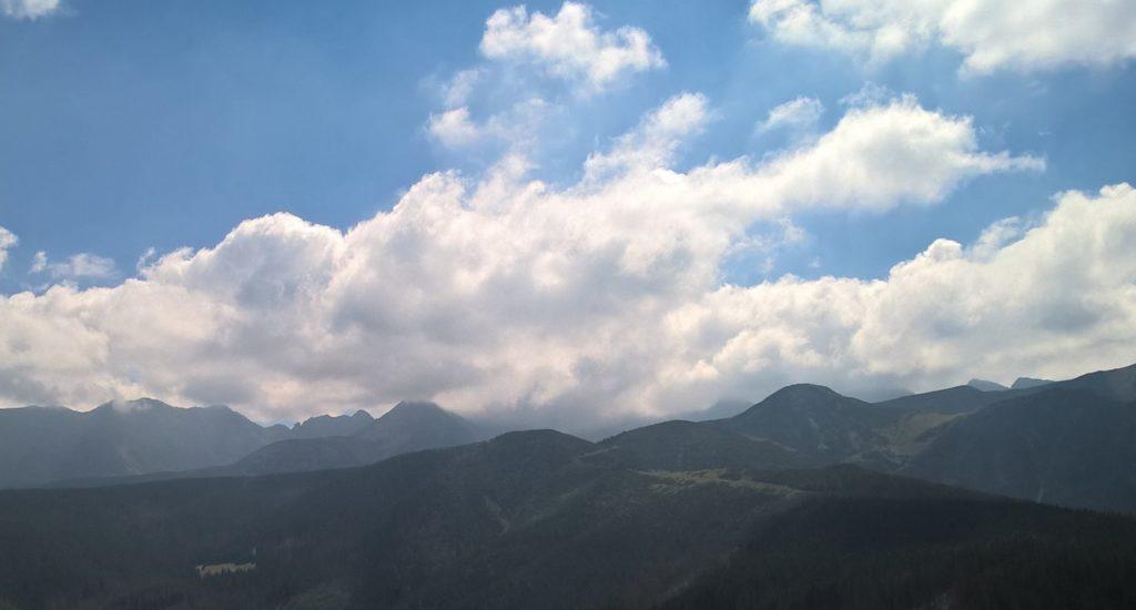pasmo gór, wyłaniających się z biało-szarych chmur, nad chmurami jasnoniebieskie niebo