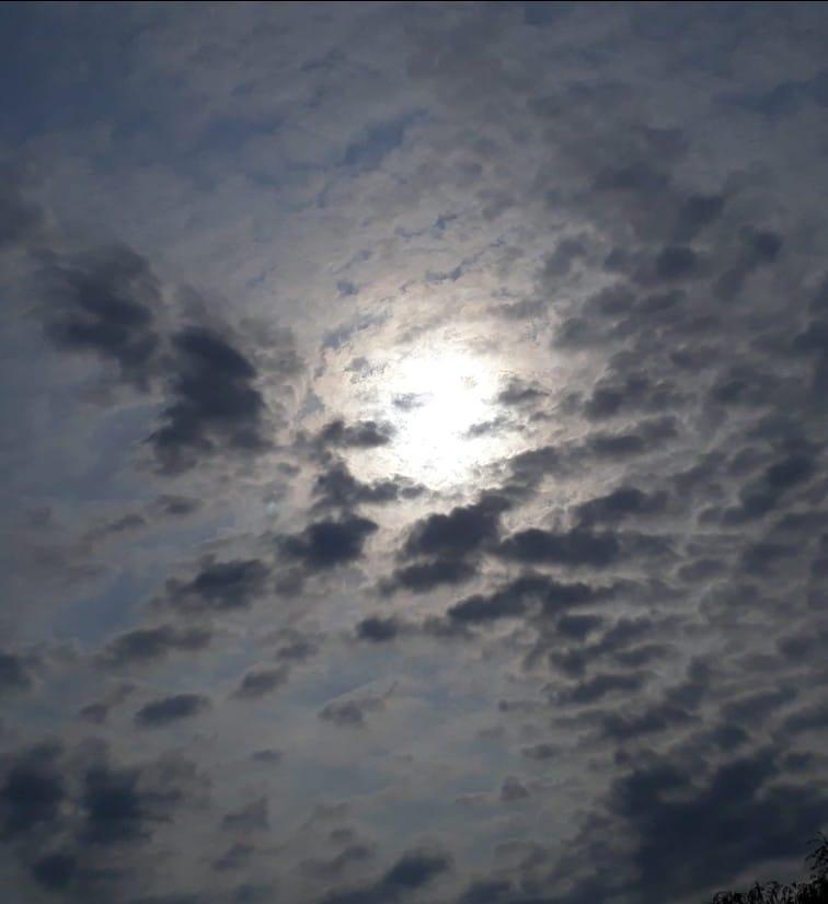 zachmurzone szare niebo, po środku rozświetlające ciemność słońce