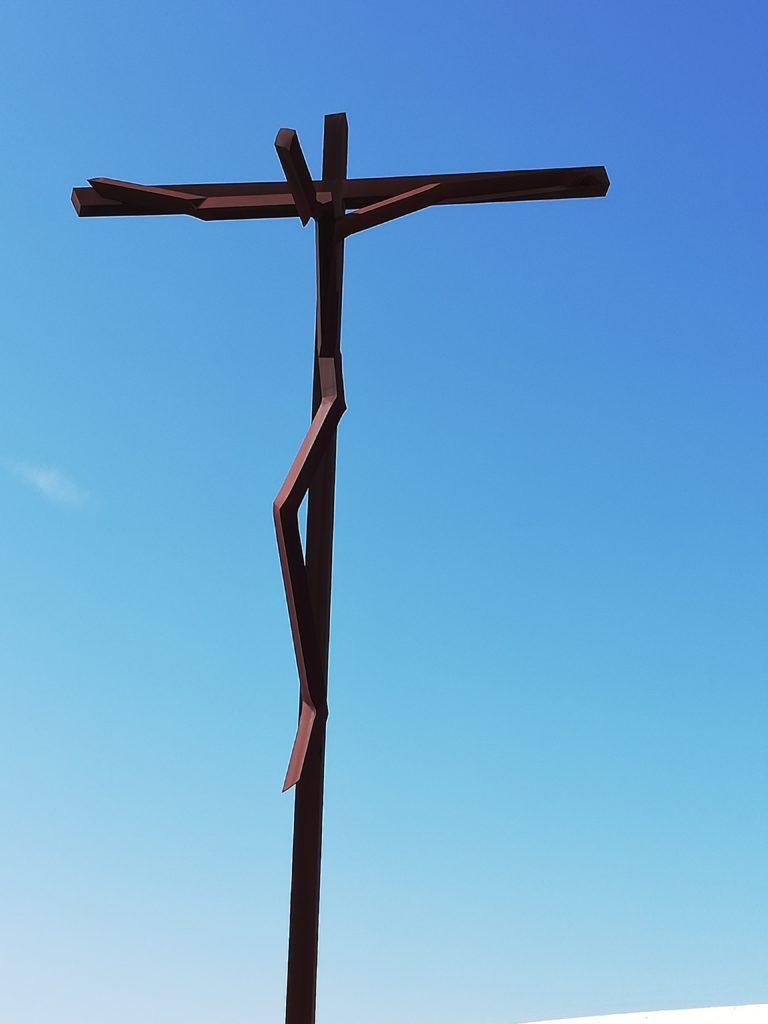 na niebieskim niebie, brązowy krzyż z Chrystusem Ukrzyżowanym - sztuka współczesna